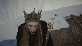 A laughing witch with a black crown on her head and a staff in her hands