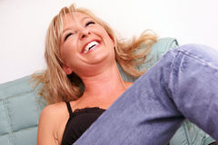 Laughing woman. A beautiful young lady is sitting on sofa with her head back laughing Royalty Free Stock Photography
