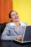 Laughing woman. Laughing business woman behind laptop royalty free stock images