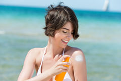 Laughing woman applying suntan lotion. To her shoulder from a spray bottle as she stands on the seashore overlooking the ocean Stock Photo