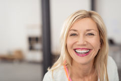 Laughing woman with beaming smile. Laughing middle-aged blond woman with beaming smile looking directly into the camera Stock Photos
