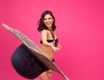 Laughing woman in bikini throwing hat at camera Royalty Free Stock Images