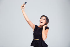 Laughing woman in black dress making selfie photo Royalty Free Stock Images