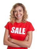 Laughing woman with blond hair in a sale shirt