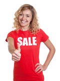 Laughing woman with blond hair in a sale shirt showing thumb Royalty Free Stock Photography
