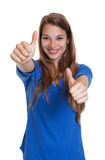 Laughing woman in a blue shirt showing both thumbs Stock Images