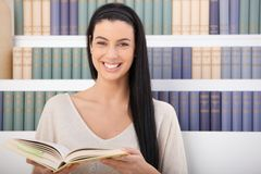 Laughing woman with book. Laughing woman sitting in front of book shelf with book handheld, looking at camera Royalty Free Stock Photos