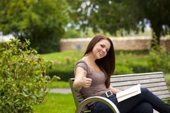 Laughing woman with book posing thumbs up Royalty Free Stock Photo