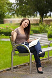 Laughing woman with book posing thumbs up Stock Photography