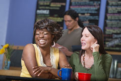 Laughing Woman in Cafe with Friend Royalty Free Stock Photos