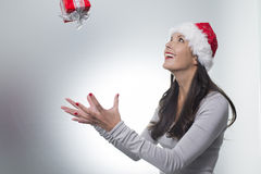 Laughing woman catching a surprise Christmas gift Stock Photos