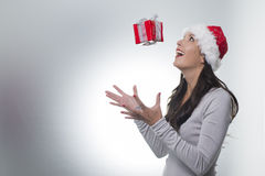 Laughing woman catching a surprise Christmas gift Stock Image