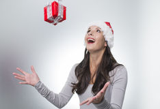 Laughing woman catching a surprise Christmas gift Royalty Free Stock Image