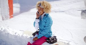 Laughing woman chatting on her mobile in snow stock video footage