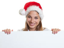 Laughing woman with christmas hat behind a signboard Royalty Free Stock Photo