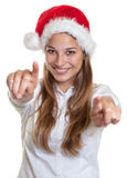 Laughing woman with christmas hat pointing at camera with two fingers stock photos