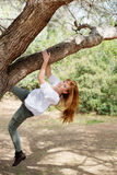 Laughing woman climbing a tree Stock Images