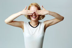 Laughing woman closing her eyes with hands Royalty Free Stock Images