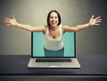 Laughing woman come out from laptop Stock Photography