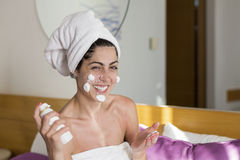 Laughing  woman with cream on her face Royalty Free Stock Images