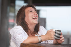 Laughing woman with a cup of drink Royalty Free Stock Images