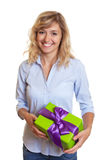 Laughing woman with curly blond hair and christmas gift Royalty Free Stock Photography