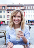 Laughing woman with curly blond hair with coffee latte macchiato Royalty Free Stock Photography