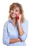 Laughing woman with curly blond hair at phone Royalty Free Stock Image