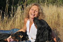 Laughing woman and dogs. Laughing young woman and her two dogs: rottweiler and french shepherd royalty free stock photo