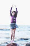 Laughing woman in dress and sweatshirt on the sea beach Royalty Free Stock Images