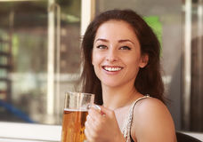 Laughing woman drinking lager beer Stock Photography
