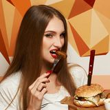 Laughing woman eating burger. Happy attractive woman holding fork and round wooden plate with appetizing burger and fried potato. Beautiful joyful female model Stock Images