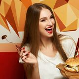 Laughing woman eating burger. Happy attractive woman holding fork and round wooden plate with appetizing burger and fried potato. Beautiful joyful female model Royalty Free Stock Photography