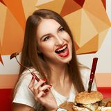 Laughing woman eating burger. Happy attractive woman holding fork and round wooden plate with appetizing burger and fried potato. Beautiful joyful female model Stock Photography