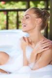 Laughing woman enjoying a bubble bath Royalty Free Stock Image