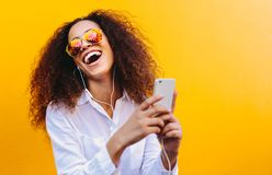 Laughing woman enjoying listening music. Laughing young woman listening to music on earphones using a cell phone. African girl with curly hair wearing sunglasses stock images