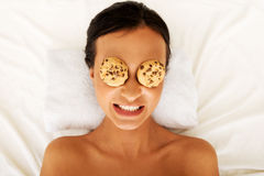 Laughing woman enjoying spa with cookies on eyes Royalty Free Stock Photos