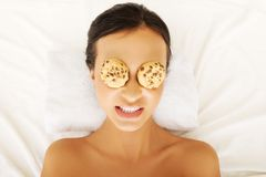 Laughing woman enjoying spa with cookies on eyes Stock Images