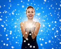 Laughing woman in evening dress holding something. Holidays, christmas and people concept - laughing woman in evening dress holding something over blue snowy Royalty Free Stock Image