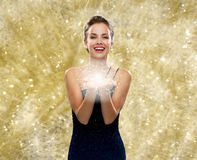 Laughing woman in evening dress holding something. Holidays, christmas and people concept - laughing woman in evening dress holding something over yellow lights Royalty Free Stock Image