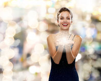 Laughing woman in evening dress holding something. Holidays and people concept - laughing woman in evening dress holding something over lights background Royalty Free Stock Photos