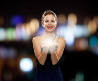 Laughing woman in evening dress holding something. Holidays and people concept - laughing woman in evening dress holding something over night lights background Royalty Free Stock Photos