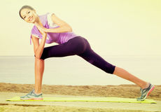 Laughing woman exercising yoga poses on beach Royalty Free Stock Photo
