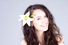 Laughing woman with flower in curly hair with smile with teeth. SPA treatment. Pretty woman with flower in curly hair with smile with teeth. SPA treatment Royalty Free Stock Images