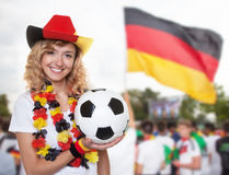 Laughing woman in german jersey with ball and other fans Stock Photo