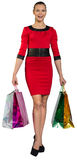 Laughing woman handing bags with right leg forward Stock Images
