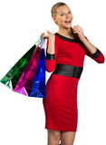 Laughing woman handing bags Stock Photo