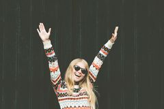 Laughing Woman happy hands up raised wellness Lifestyle fashion emotional girl wearing cozy sweater against wooden black Royalty Free Stock Images