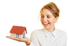 Laughing woman has household insurance. Laughing woman has home insurance with a small house on hand Royalty Free Stock Photo