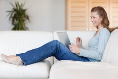 Laughing woman with her laptop on the sofa Royalty Free Stock Images